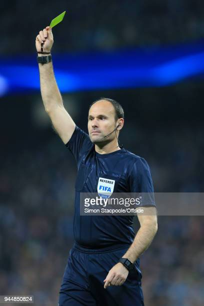 Referee Antonio Miguel Mateu Lahoz issues a yellow card during the UEFA Champions League Quarter Final Second Leg match between Manchester City and...