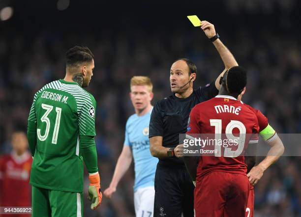 Referee Antonio Miguel Mateu Lahoz shows Sadio Mane of Liverpool a yellow card during the UEFA Champions League Quarter Final Second Leg match...