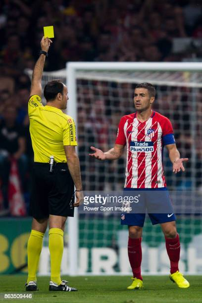 Referee Antonio Miguel Mateu Lahoz shows the yellow card to Gabriel Fernandez Arenas Gabi of Atletico de Madrid during the La Liga 201718 match...