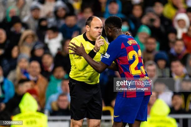 Referee Antonio Miguel Mateu Lahoz talks to Samuel Umtiti of FC Barcelona during the Liga match between Real Madrid CF and FC Barcelona at Estadio...