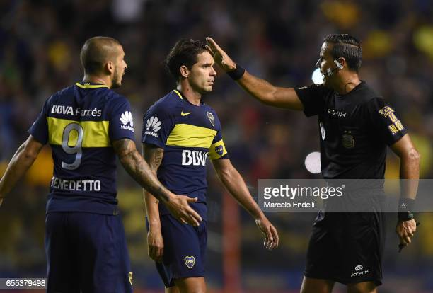 Referee Ariel Panel argues with Fernando Gago and Dario Benedetto of Boca Juniors during a match between Boca Juniors and Talleres as part of Torneo...