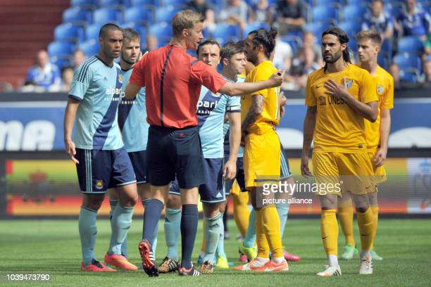 Referee Arne Aarnink mediates in a confrontation between West Ham's Winston Reid and Malaga's Sergio Sanchez during the Schalke Cup soccer test match...