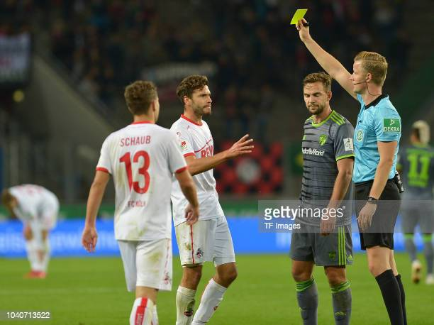 Referee Arne Aarnink shows a yellow card to Jonas Hector of FC Koeln during the Second Bundesliga match between 1 FC Koeln and FC Ingolstadt 04 at...