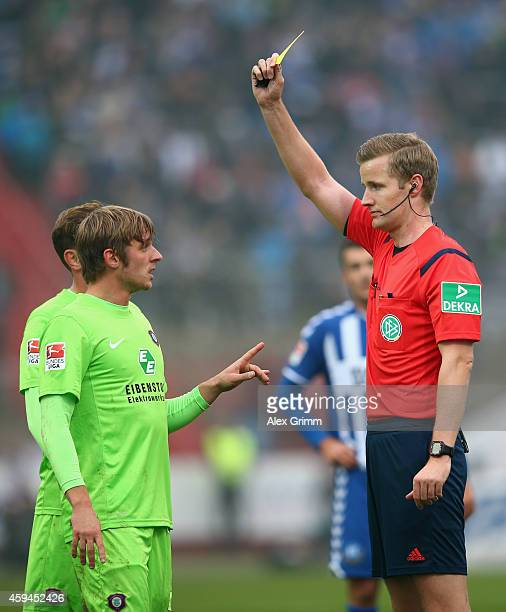 Referee Arne Aarnink shows the yellow card to Arvydas Novikovas during the Second Bundesliga match between Karlsruher SC and Erzgebirge Aue at...