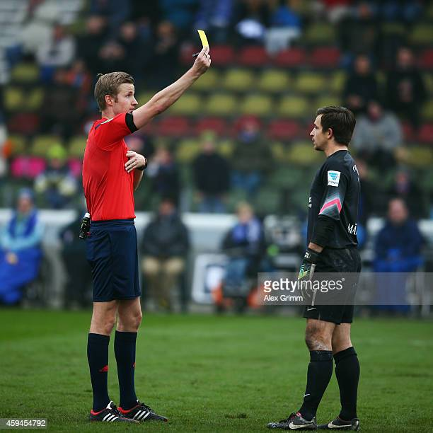 Referee Arne Aarnink shows the yellow card to goalkeeper Martin Maennel of Aue during the Second Bundesliga match between Karlsruher SC and...