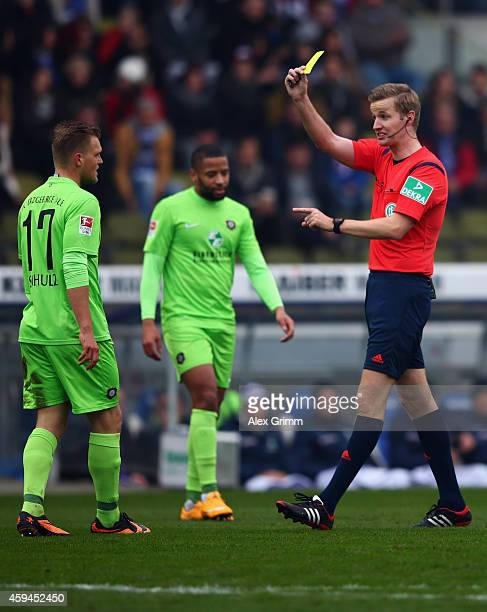 Referee Arne Aarnink shows the yellow card to Thorsten Schulz during the Second Bundesliga match between Karlsruher SC and Erzgebirge Aue at Wildpark...
