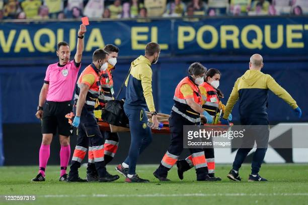 Referee Artur Dias gives a second yellow and red card to Etienne Capoue of Villarreal who leaves the pitch injured on a stretcher during the UEFA...