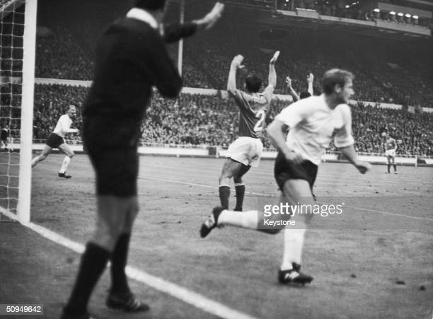 Referee Arturo Yamasaki points to the centre line as he awards first goal to England in a World Cup match against France held at Wembley 21st July...