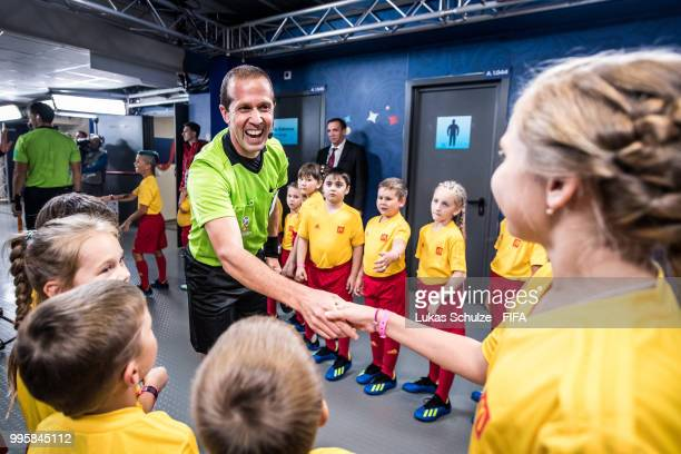 Referee assistant Mauricio Espinosa greets the escot kids of McDonalds prior to the 2018 FIFA World Cup Russia Semi Final match between Belgium and...
