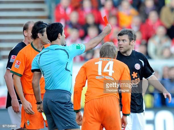 Referee Babak Rafati shows Florian Heller the red card during the Bundesliga match between FSV Mainz 05 and SV Werder Bremen at Bruchweg Stadium on...