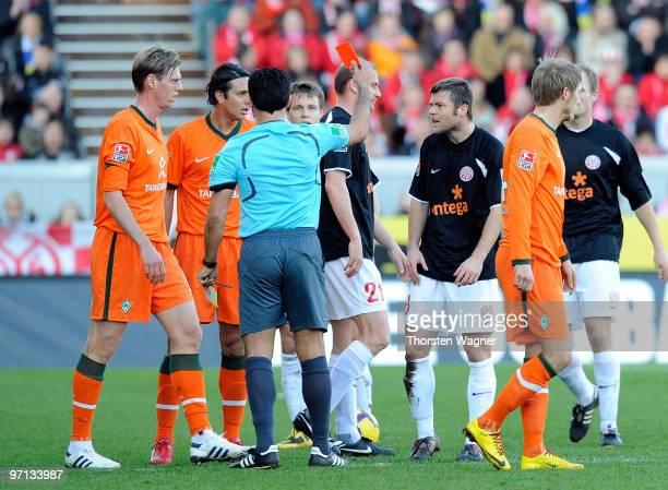 Referee Babak Rafati shows the red card to Florian Heller during the Bundesliga match between FSV Mainz 05 and SV Werder Bremen at Bruchweg Stadium...