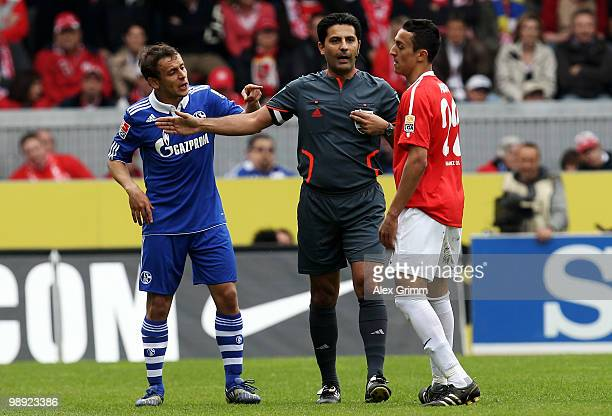 Referee Babak Rafati stands between Rafinha of Schalke and Chadli Amri of Mainz during the Bundesliga match between FSV Mainz 05 and FC Schalke 04 at...