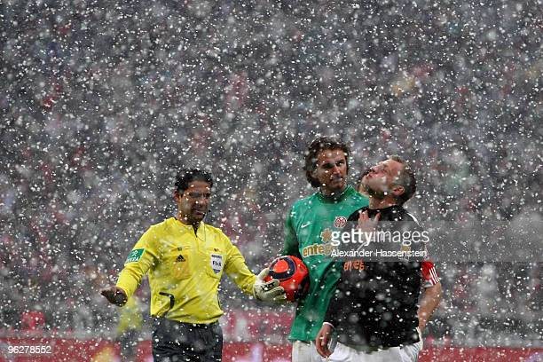 Referee Babak Rafati talks to the players during heavy snowfall at the Bundesliga match between FC Bayern Muenchen and FSV Mainz 05 at Allianz Arena...