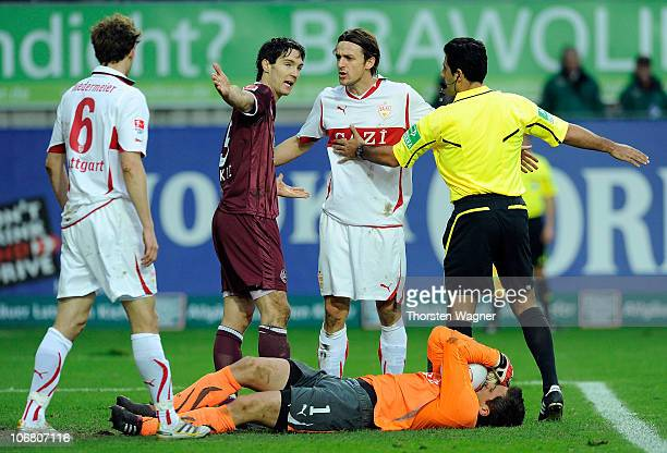 Referee Babak Rafati talks with the players of both teams during the Bundesliga match between 1FC Kaiserslautern and VFB Stuttgart at...