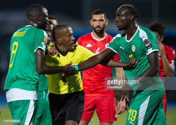 Referee BAMLAK TESSEMA pushes away Cheikhou Kouyate and Mbaye Diagne of Senegal after awarding Tunisia a penalty during the 2019 Africa Cup of...