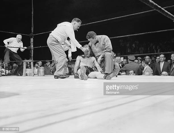 Referee Barney Felix props up the unconscious Bronx fighter Frankie Ryff as a handler sponges his face in an attempt to revive him Ryff was knocked...