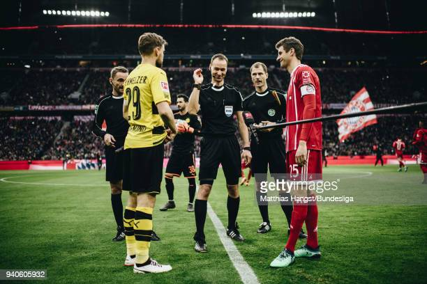 Referee Bastian Dankert performs the coin toss with Marcel Schmelzer of Dortmund and Thomas Mueller of FC Bayern Muenchen during the Bundesliga match...