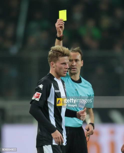 Referee Bastian Dankert shows a yellow card to Nico Elvedi of Moenchengladbach during the Bundesliga match between Borussia Moenchengladbach and...