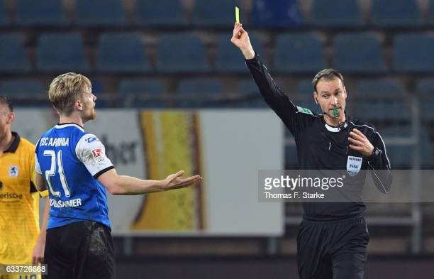 Referee Bastian Dankert shows the yellow card to Andreas Voglsammer of Bielefeld during the Second Bundesliga match between DSC Arminia Bielefeld and...