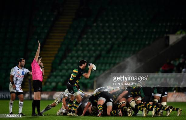 Referee Ben Whitehouse overseas a srum as Northampton Saints' English scrum-half James Mitchell prepares to place the ball during the European Rugby...
