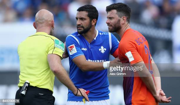 Referee Benedikt Kempkes discusses with Aytac Sulu of Darmstadt and Tim Hoogland of Bochum during the Second Bundesliga match between SV Darmstadt 98...