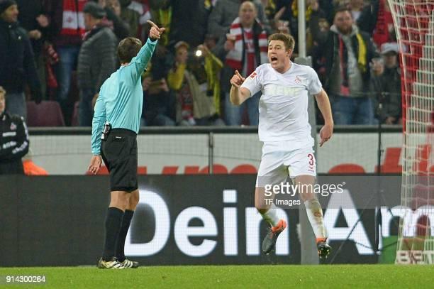 Referee Benjamin Brand and Dominique Heintz of Koeln gesture during the Bundesliga match between 1 FC Koeln and Borussia Dortmund at...