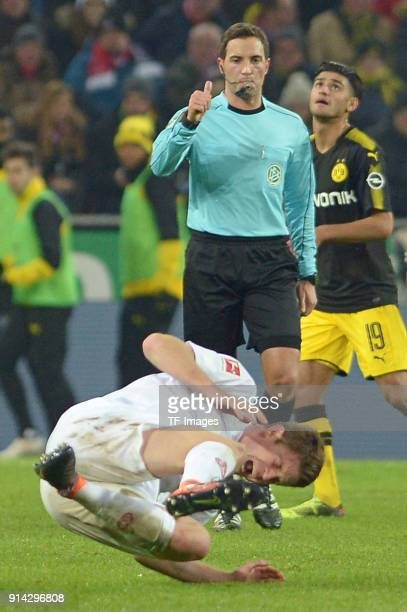 Referee Benjamin Brand gestures and Simon Terodde of Koeln on the ground during the Bundesliga match between 1 FC Koeln and Borussia Dortmund at...