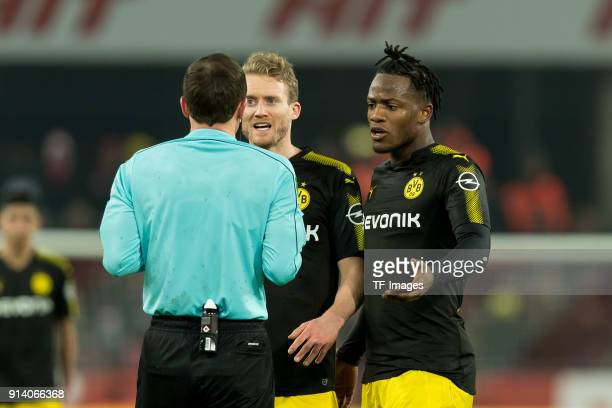Referee Benjamin Brand speaks with Andre Schuerrle of Dortmund and Michy Batshuayi of Dortmund during the Bundesliga match between 1 FC Koeln and...