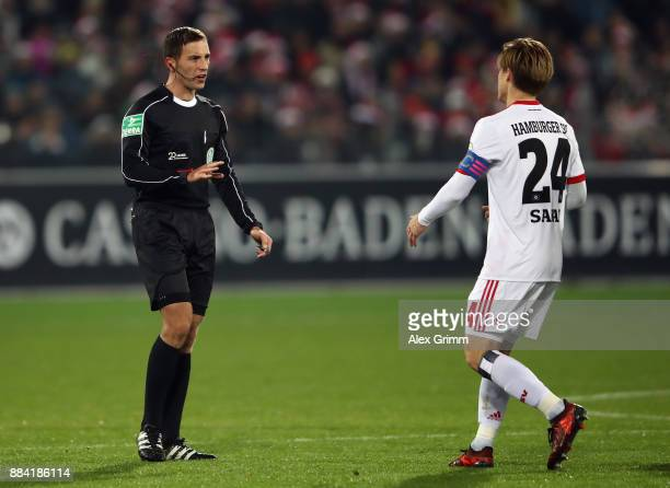 Referee Benjamin Brand talks to Gotoku Sakai of Hamburg during the Bundesliga match between SportClub Freiburg and Hamburger SV at SchwarzwaldStadion...