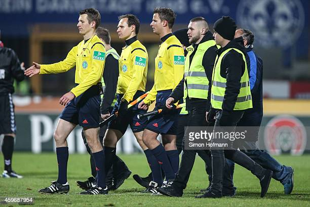 Referee Benjamin cortus and his assistants Daniel Schlager and Johannes Huber are escorted by stewards as they leave the pitch after the Second...