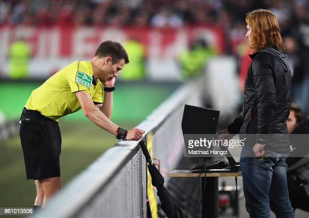 Referee Benjamin Cortus looks at the video replay to make a decision on a penalty during the Bundesliga match between VfB Stuttgart and 1 FC Koeln at...
