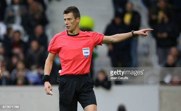 Referee Benoit Bastien of France gives a yellow card to Maya Yoshida of Japan and a penalty for Brazil after using the video during the international...