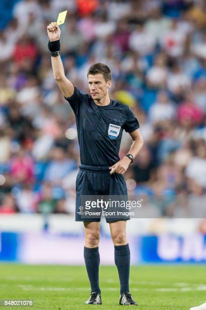 Referee Benoit Bastien shows Agustin Farias of APOEL FC the yellow card during the UEFA Champions League 201718 match between Real Madrid and APOEL...