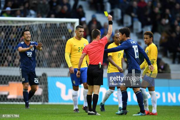 Referee Benoit Bastien shows an yellow card to Hiroki Sakai of Japan during the international friendly match between Brazil and Japan at Stade...