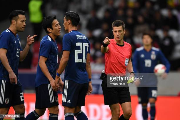 Referee Benoit Bastien shows an yellow card to Maya Yoshida of Japan during the international friendly match between Brazil and Japan at Stade...