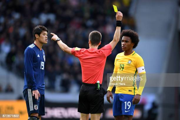 Referee Benoit Bastien shows an yellow card to Willian during the international friendly match between Brazil and Japan at Stade PierreMauroy on...