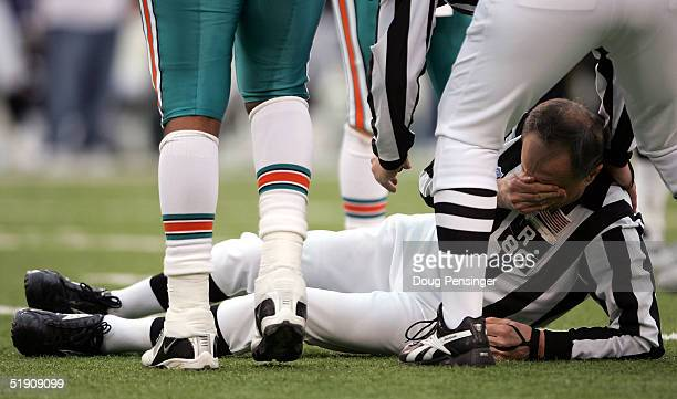Referee Bernie Kukar is aided by a member of his crew as he tries to collect himself after colliding with a member of the Miami Dolphins as the...