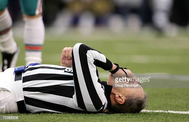 Referee Bernie Kukar tries to collect himself after colliding with a member of the Miami Dolphins as the Baltimore Ravens defeated the Dolphins 3023...