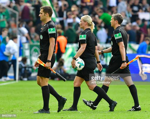 Referee Bibiana Steinhaus and linesmen leave the pitch for the halftime break during the German first division Bundesliga football match between...