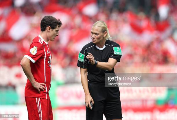 Referee Bibiana Steinhaus chats with Sebastian Rudy of Muenchen during the DFB Cup first round match between Chemnitzer FC and FC Bayern Muenchen at...