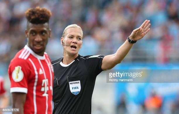 Referee Bibiana Steinhaus gestures next to Kingsley Coman of Muenchen during the DFB Cup first round match between Chemnitzer FC and FC Bayern...