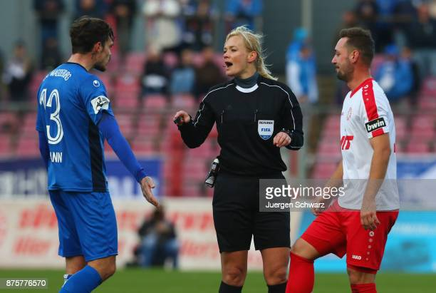 Referee Bibiana Steinhaus gives instructions to Dennis Erdmann of Magdeburg and Maik Kegel of Cologne during the 3 Liga match between SC Fortuna...