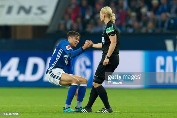 Referee Bibiana Steinhaus helps Amine Harit of Schalke during the Bundesliga match between FC Schalke 04 and 1 FSV Mainz 05 at VeltinsArena on...