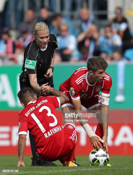 Referee Bibiana Steinhaus helps Rafinha of Muenchen next to Thomas Mueller of Muenchen during the DFB Cup first round match between Chemnitzer FC and...