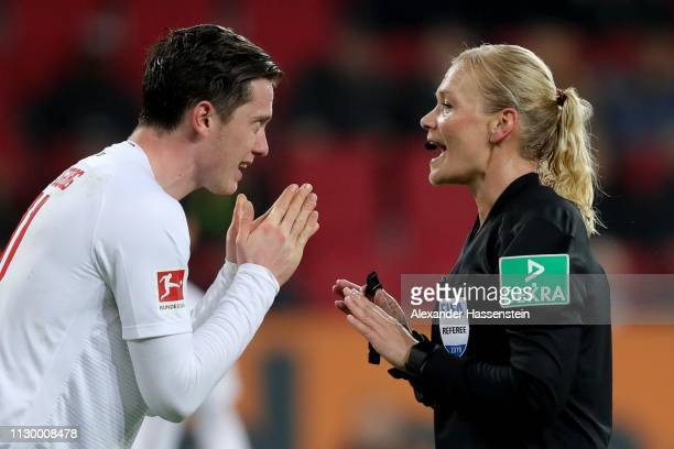Referee Bibiana Steinhaus reacts to Michael Gregoritsch of Augsburg during the Bundesliga match between FC Augsburg and FC Bayern Muenchen at...