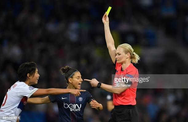Referee Bibiana Steinhaus shows a yellow card to Saki Kumagai of Olympique Lyonnais as Veronica Boquete of Paris SaintGermain Feminines looks on...