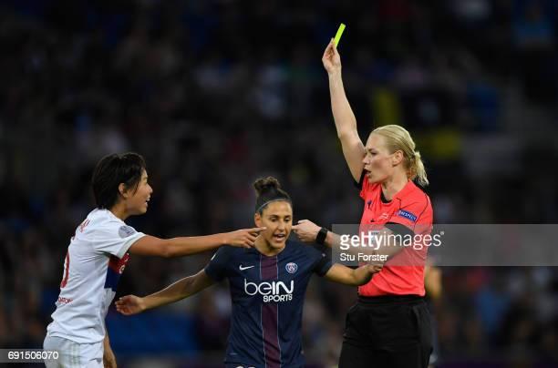 Referee Bibiana Steinhaus shows a yellow card to Saki Kumagai of Olympique Lyonnais as Veronica Boquete of Paris SaintGermain Feminines looks on...