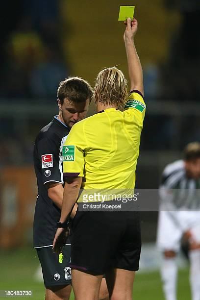 Referee Bibiana Steinhaus shows Stephan Hain of Muenchen the yellow card during the Second Bundesliga match between VfR Aalen and 1860 Muenchen at...