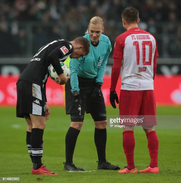 Referee Bibiana Steinhaus sprays a line next to Thorgan Hazard of Moenchengladbach and Daniel Baier of Augsburg during the Bundesliga match between...