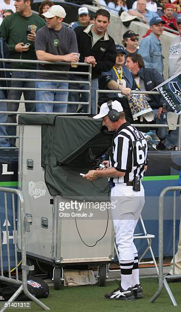 Referee Bill Corollo reviews an instant replay on video during the game between the San Francisco 49ers and the Seattle Seahawks at Qwest Field on...